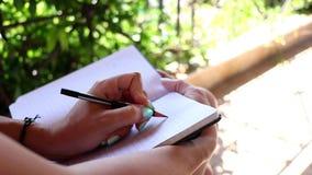 在她的笔记本的妇女文字在她的阳台 采取关于她的日志特写镜头的女性笔记 股票录像