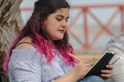 在她的笔记本的美好的胖的妇女文字笔记的画象 免版税库存照片