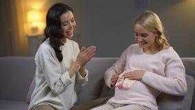 在她的腹部,与朋友的婴儿送礼会的微笑的孕妇藏品婴孩袜子 股票视频