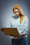 在她的膝上型计算机的内容憎恶的年轻女商人 免版税图库摄影