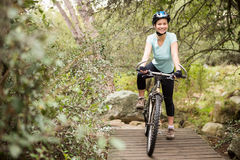 在她的自行车的微笑的适合的妇女休假 免版税图库摄影