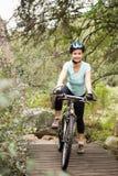 在她的自行车的微笑的适合的妇女休假 免版税库存照片