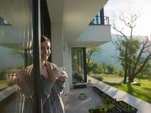 在她的豪华家庭别墅前面的妇女饮用的咖啡 库存照片