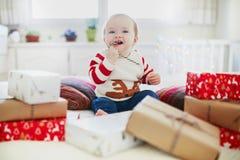 在她的首先圣诞节的愉快的一点女婴打开的圣诞礼物 库存照片