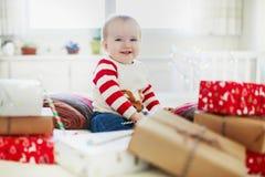 在她的首先圣诞节的愉快的一点女婴打开的圣诞礼物 免版税图库摄影