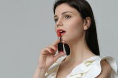 在她的嘴唇附近拿着一支唇膏一个逗人喜爱的女孩的画象 图库摄影