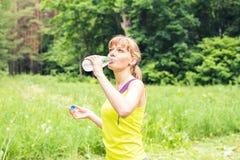 在她的锻炼以后的年轻美丽的适合妇女饮料水 免版税图库摄影