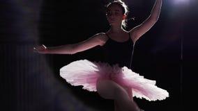 在她的pointe芭蕾舞鞋的灵活的女孩跳舞在黑背景的聚光灯在演播室 专业年轻 影视素材