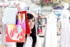 在她隐藏的购物微笑的妇女之后的袋子 库存图片