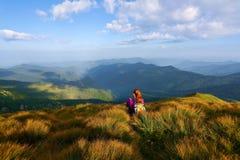 在好的绿色小丘中有坐在止步不前和观看与beatufil山的一个红色头发女孩天际 免版税图库摄影