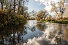 在好秋天天期间,有天空反映,五颜六色的树和天空蔚蓝的Tiver附庸国与云彩 图库摄影