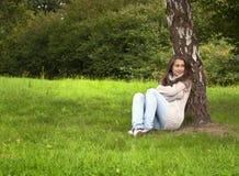 在妇女之下的坐的结构树 库存图片