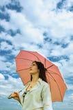 在妇女之下的桃红色伞 库存图片