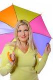 在妇女之下的秋天俏丽的常设伞 免版税库存照片