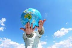 在妇女之下的蓝色地球藏品天空 免版税图库摄影