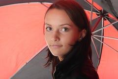 在妇女之下的黑色红色伞 免版税库存照片
