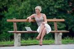 在妇女之外的膝上型计算机 免版税库存图片