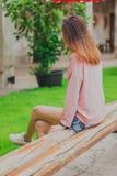 在妇女后坐一把长的木椅子 库存照片