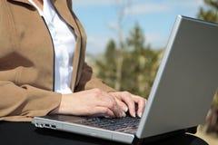 在妇女工作之外的膝上型计算机 免版税库存图片
