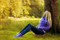 在妇女年轻人之下的坐的结构树 库存图片