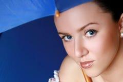在妇女年轻人之下的蓝色黑暗的伞 免版税库存照片