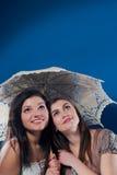在妇女年轻人之下的隐藏的微笑的二伞 图库摄影