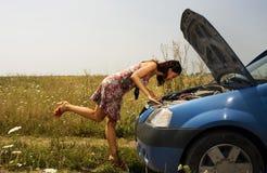 在妇女年轻人的弯的汽车 库存图片