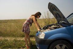 在妇女年轻人附近的残破的汽车 免版税库存图片