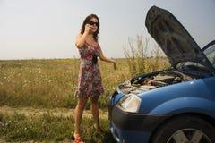 在妇女年轻人附近的残破的汽车 库存图片