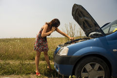 在妇女年轻人附近的残破的汽车 库存照片