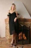 在妇女年轻人附近的美丽的壁炉 库存图片
