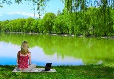 在妇女年轻人附近的美丽的湖膝上型计算机 免版税库存照片