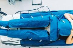 在妇女患者的腿pressotherapy机器在医院病床上 免版税库存图片