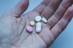 在妇女手上的五颜六色的药片 免版税库存照片