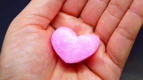 在妇女手上的桃红色心脏 库存图片