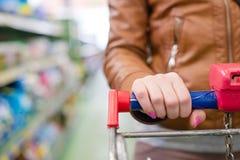 在妇女手上的特写镜头图象在拿着台车的超级市场运载与在背景的购物架子 免版税库存图片