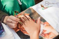 在妇女手,皮肤装饰上的Mehndi应用 免版税图库摄影