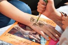 在妇女手,皮肤装饰上的Mehndi应用 免版税库存照片