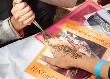 在妇女手,皮肤装饰上的Mehndi应用 图库摄影