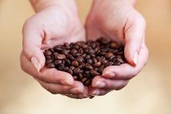 在妇女掌上型计算机的咖啡豆 免版税库存图片
