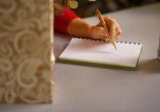 在妇女文字的特写镜头在笔记本名单 免版税库存图片