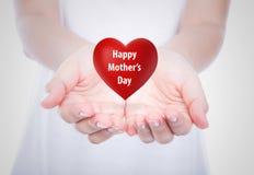 在妇女的愉快的母亲节红色心脏移交被隔绝的身体 库存图片