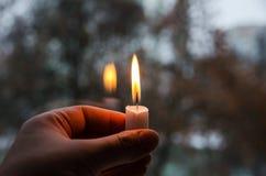 在妇女的手上点燃的一个蜡烛 免版税库存图片