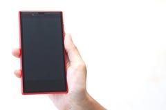 在妇女的手上的红色手机 图库摄影