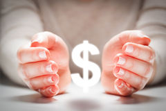 在妇女的手之间的美元的符号在保护姿态  货币稳定 免版税库存图片