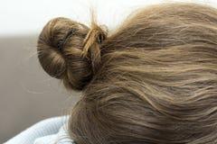 在妇女的深色的头发的上部小圆面包特写镜头 图库摄影