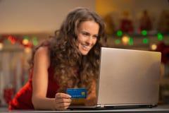 在妇女的特写镜头有使用膝上型计算机的信用卡的 库存图片