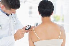 在妇女的皮肤病学家审查的黑瘤 免版税图库摄影
