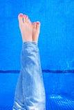 在妇女的看法上放松由游泳池的蓝色牛仔裤的 免版税库存照片