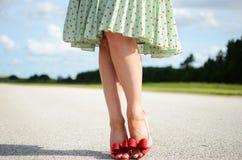 在妇女的脚的红色短剑鞋子 免版税图库摄影